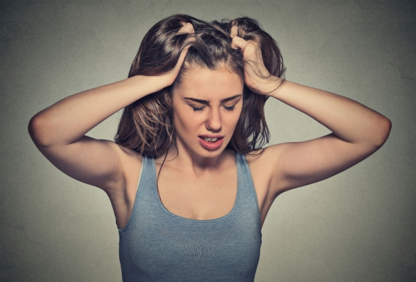 43705176 - frustrated stressed young woman. headshot unhappy overwhelmed girl having headache bad day pulling her hair out isolated on grey wall background. negative emotion face expression feelings perception