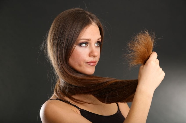 19034494 - beautiful woman holding split ends of her long hair,  on black background