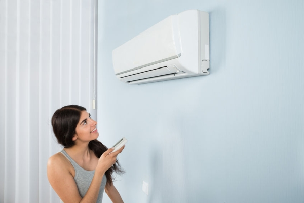 39653653 - young happy woman holding remote control air conditioner in house