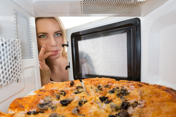 41512552 - girl looking at a pizza in the microwave