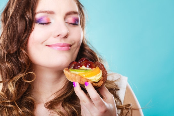 41443774 - bakery sweet food and people concept. content attractive woman closed eyes holds cake cupcake in hand smelling blue background