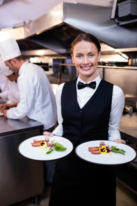 Waitress showing dishes to the camera and team of chefs working in background