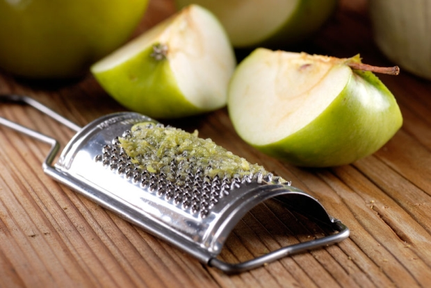 33943205 - grated apple with tool stainless on wood table