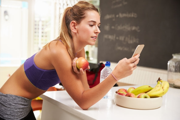 41146872 - woman wearing gym clothing looking at mobile phone
