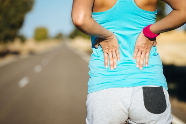 25965475 - female runner athlete back injury and pain. woman suffering from painful lumbago or kidney illness while running in rural road.