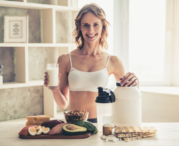 79149197 - beautiful young sportswoman is looking at camera and smiling while preparing sport nutrition in kitchen at home