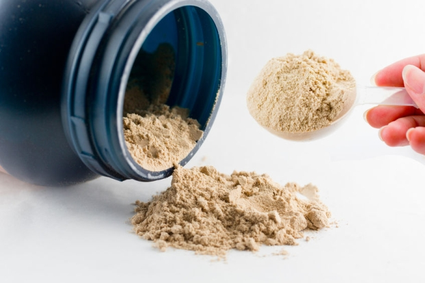 39157372 - the hand raise a spoon measure whey protein chocolate powder for fitness and bodybuilding gaining muscle.