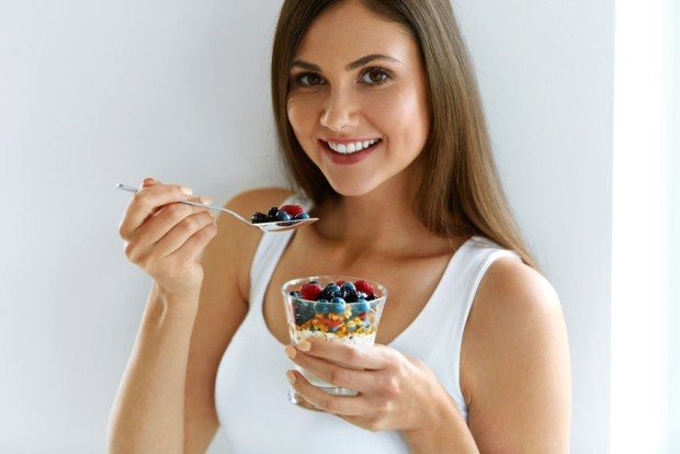 68361787 - healthy weight loss food. portrait of pretty smiling fit girl having yogurt, berries and oatmeal. beautiful young woman eating fresh yoghurt, berries and granola for breakfast. diet nutrition concept