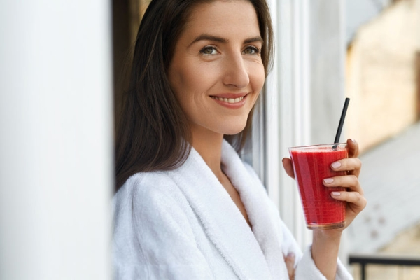 59969813 - detox diet. healthy woman drinking juice for breakfast in morning. beautiful smiling vegan girl in bathrobe holding fresh vegetable smoothie drink. fitness food, dieting weight loss nutrition concepts
