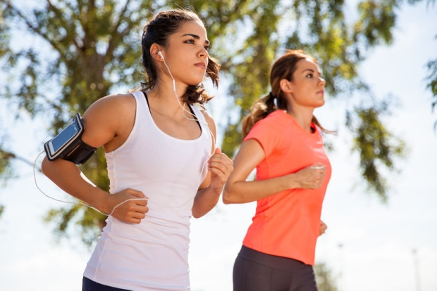 31232442 - two female runners working out while listening to music on their mobile phone on an armband