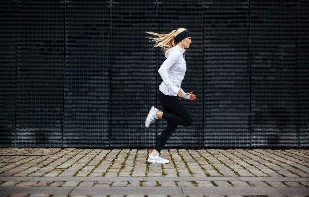 35324990 - side view of sporty young woman running on sidewalk in morning. health conscious concept with copy space.