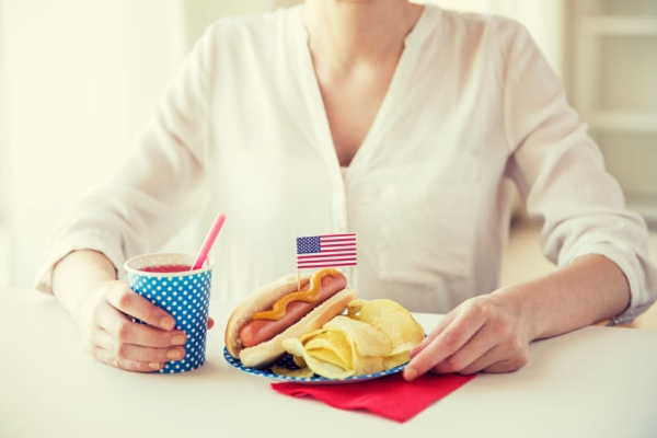 61649042 - independence day, celebration, patriotism and holidays concept - close up of woman eating hot dog with american flag decoration and potato chips, drinking juice and celebrating 4th july at home party