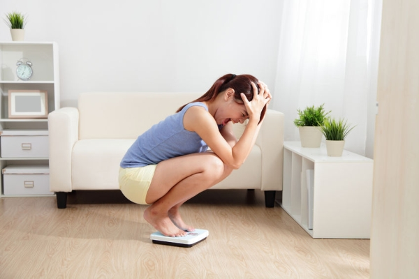 25756903 - upset woman on weigh scale at home, asian