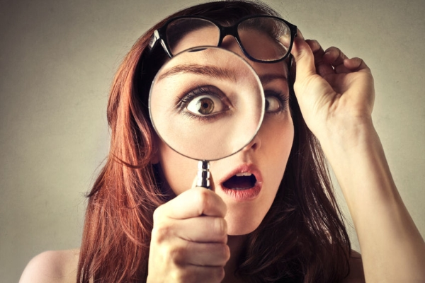 50740157 - young woman looking through magnifying glass