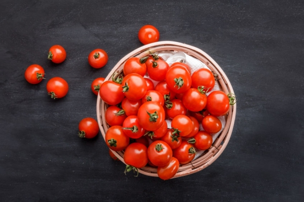 45374769 - full top view of pile of cherry tomatoes in a rattan basket on black board for background