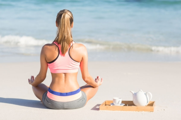 44847596 - fit woman doing yoga beside the sea at the beach