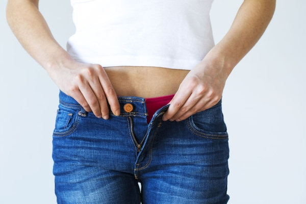 72214799 - weight gain woman getting dressed wearing jeans