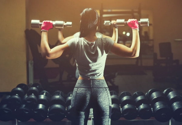 79178763 - slim bodybuilder girl lifts heavy dumbbell standing in front of the mirror while training in the gym. sports concept fat burning and a healthy lifestyle.