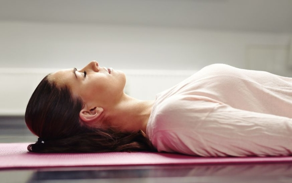 29910461 - close up image of young woman lying on a yoga mat with her eyes closed in meditation.