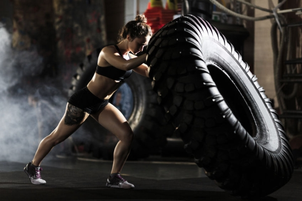 59969620 - strong fit woman flipping tire in gym