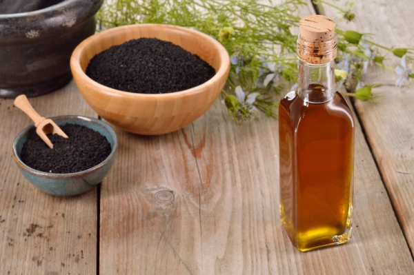 31283535 - nigella sativa oil in a bottle and nigella seeds and flowers on wooden background. black cumin healing herb. cold pressed, non refined oil. traditional medicine.