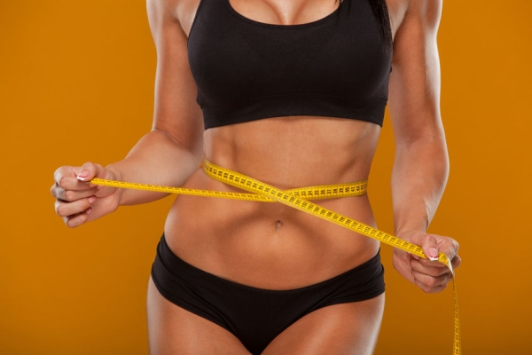 48702983 - sport, fitness and diet concept - close up of trained belly with measuring tape.
