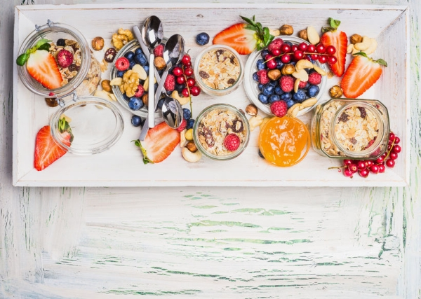 54990983 - healthy breakfast with muesli and summer berries and nuts. fresh granola, muesli and berries in glass jars on light shabby chic wooden background, top view, place for text
