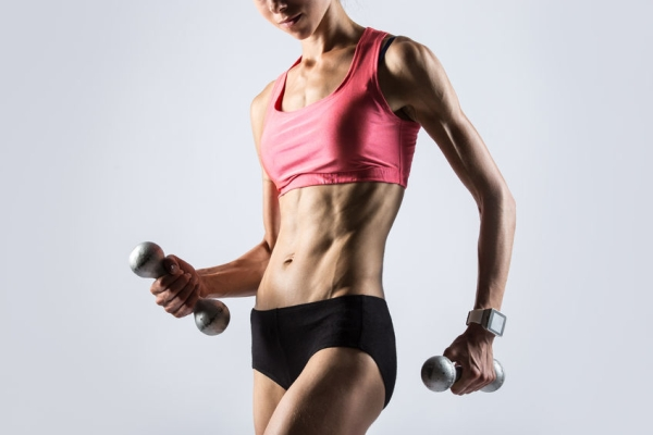 63418818 - attractive young fitness person wearing smartwatch and red sportswear top lifting dumbbells. serious sporty model girl working out, doing weight training with dumbbells on grey background. close-up