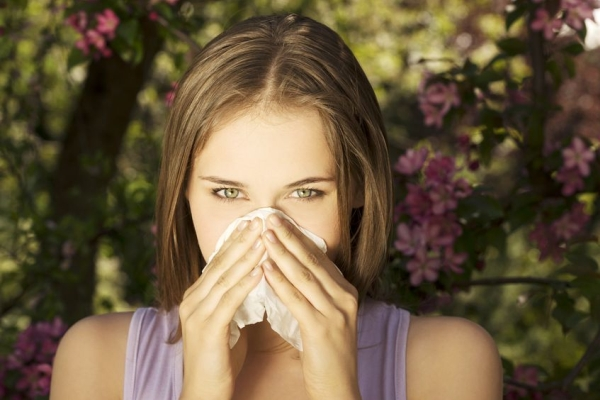 22465773 - young woman with allergy during sunny day is wiping her nose.