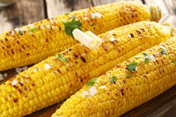 44384209 - fresh tasty grilled corn with butter on brown table