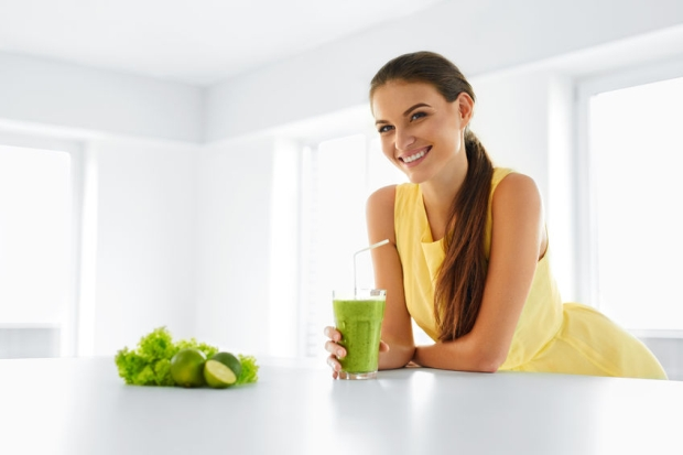48201190 - healthy meal. happy beautiful smiling woman drinking green detox vegetable smoothie. healthy lifestyle, food and eating. drink juice. diet, health and beauty concept.
