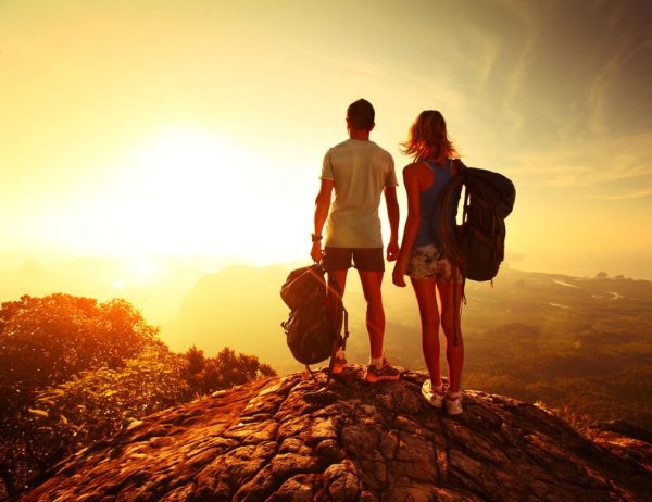 25581330 - hikers with backpacks relaxing on top of a mountain and enjoying valley view