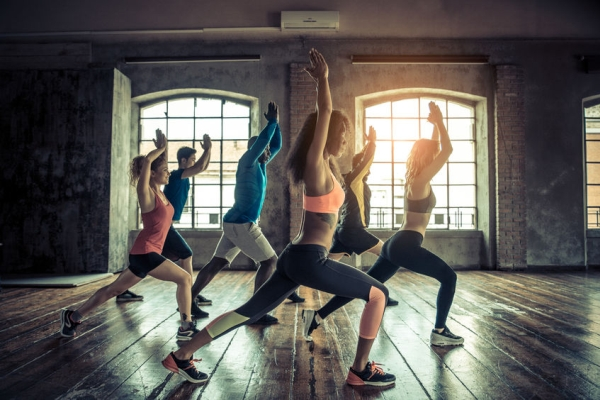 57814540 - group of sportive people in a gym training - multiracial group of athletes stretching before starting a workout session