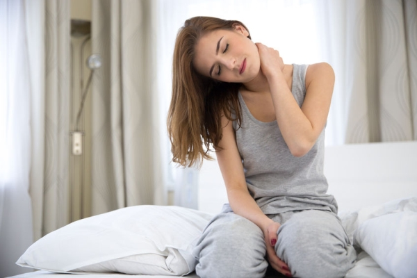 36707462 - young woman sitting on the bed with pain in neck