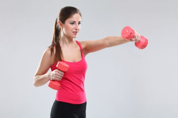 19165073 - beautiful caucasian woman in fitness wear with dumbbells over background