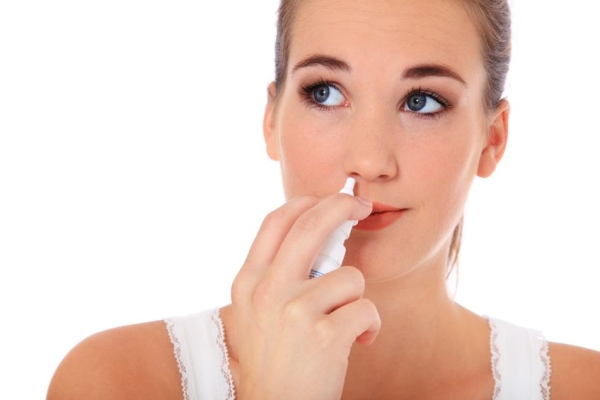 10334123 - attractive young woman using nasal spray. all on white background.