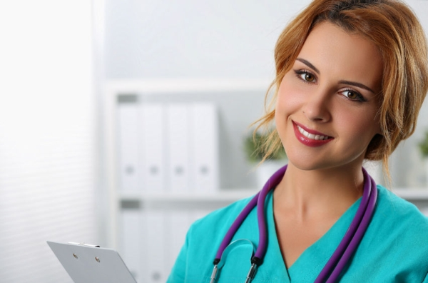 42963536 - beautiful charming friendly smiling female medicine therapeutist doctor standing in office, holding document pad and looking in camera. medical help, physician reception or insurance concept
