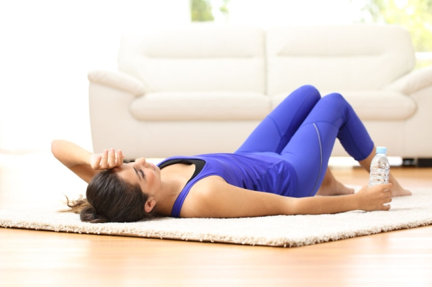 50573138 - tired sportswoman lying on the floor at home after sport