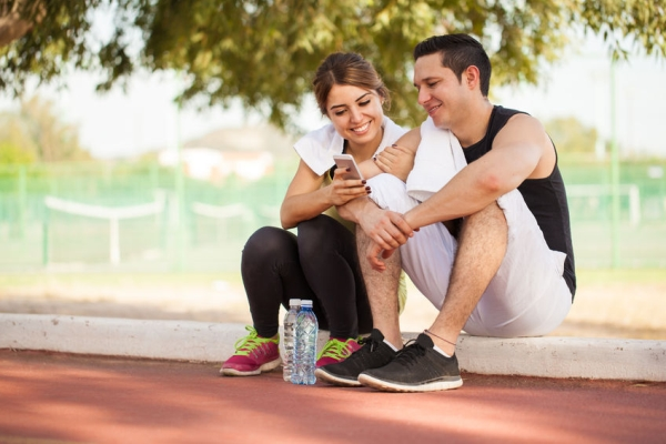 48290727 - portrait of a young couple taking a break from exercising together and looking at some pictures on a smartphone