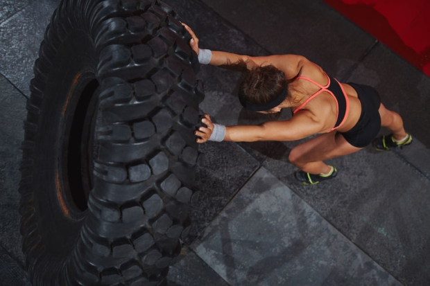 50876100 - strong sporty woman flipping tyre