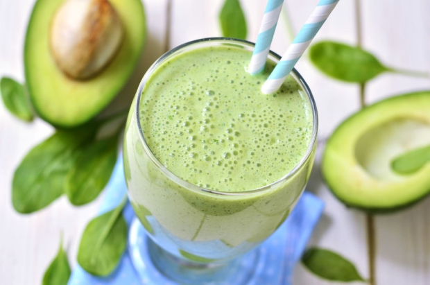 47102303 - avocado and spinach green smoothie ona light wooden table.