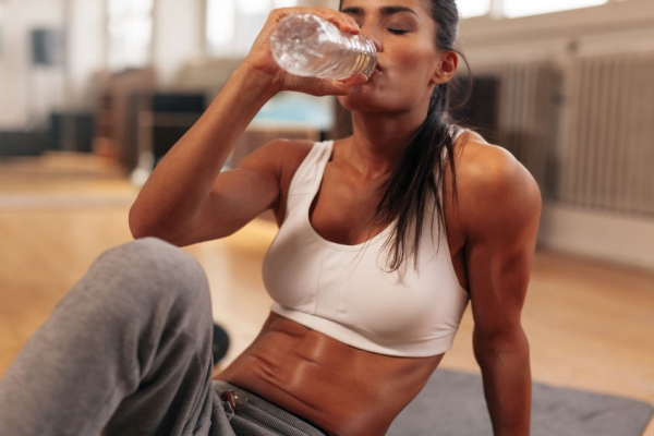 43852676 - fitness woman drinking water from bottle. muscular young female at gym taking a break from workout.