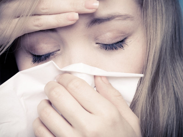 26861143 - flu cold or allergy symptom. closeup of sick young woman girl with fever sneezing in tissue. health care. studio shot. black and white photo.