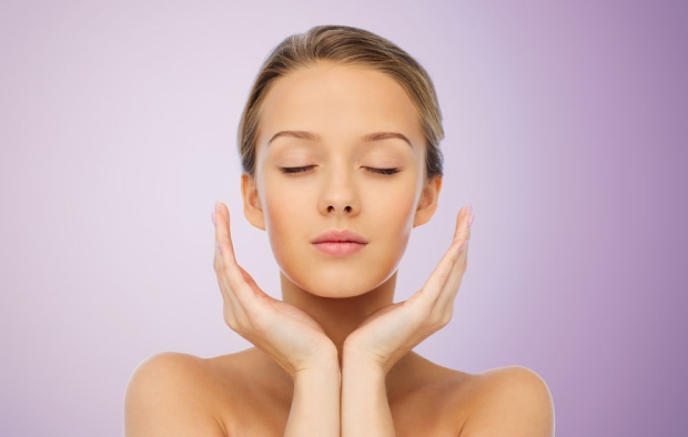 52917275 - beauty, people, skincare and health concept - young woman face and hands over violet background