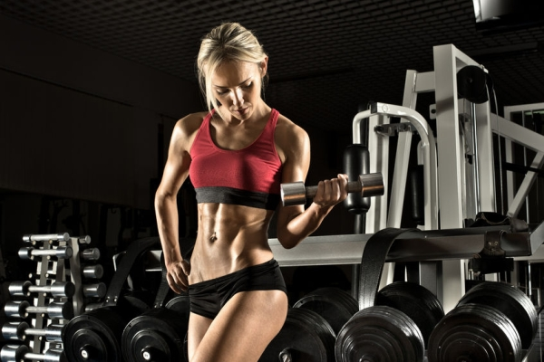 39292522 - beautiful girl bodybuilder ,  execute exercise with  dumbbells, in dark gym
