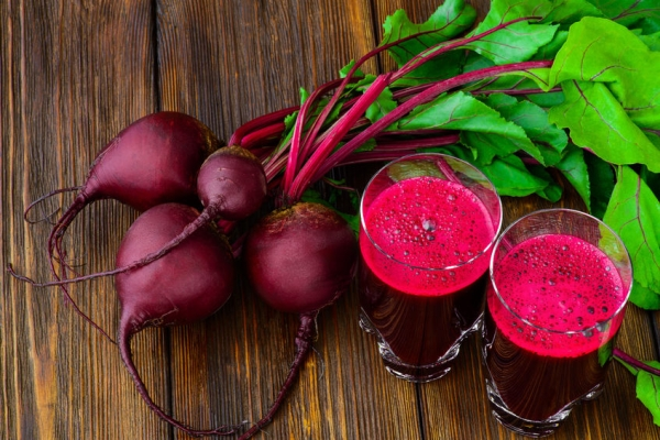 41778912 - glass of fresh beetroot juice with bets on wooden table.