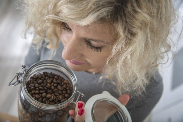 65827501 - blonde girl with curly hair is smelling coffee beans in glass pot