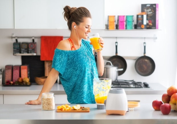 35810638 - happy fitness young woman drinking pumpkin smoothie in kitchen
