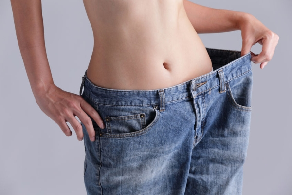 40856623 - woman shows weight loss by wearing old jeans, asian beauty