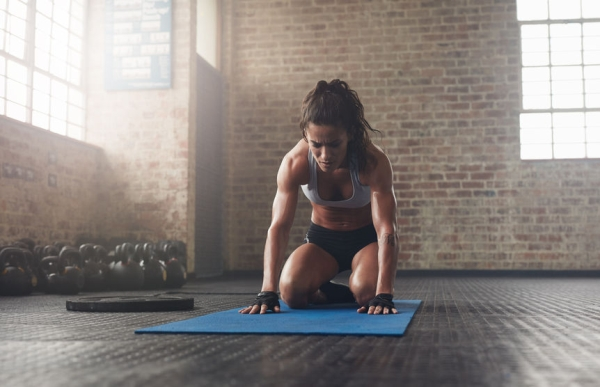 58559458 - indoor shot of young woman doing a forward bend exercise on fitness mat. muscular young athlete doing pilates workout at the gym.